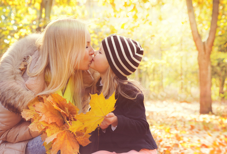 kiss love: Happy daughter kissing her mother in autumn park and play collects a bouquet of yellow maple leaves.