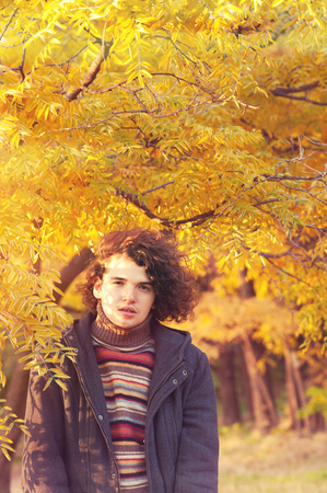 oudoor: Young attractive calm man portrait dressed in gray jacket and striped sweater, standing oudoor in autumn park.