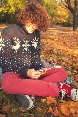 red jeans: Young adult man dressed in knit sweater with deers, knit shoes and red jeans, have a leisure sitting in autumn park and reading the electronic book.