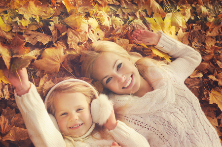 sweater girl: Happy smiling caucasian blonde mother and daughter dressed in white knitted sweaters, lying in yellow autumn foliage, top view, leisure in autumn park.