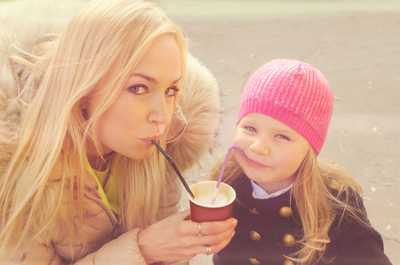 milkshake: Cute young mother with daughter have a fun drinking a milkshake from the same paper cup using a tubes.