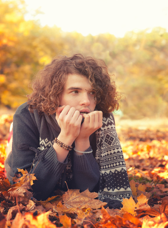 male hair: Stylish man in knit sweater and scarf lying on autumn leaves, oudoor in autumn park.