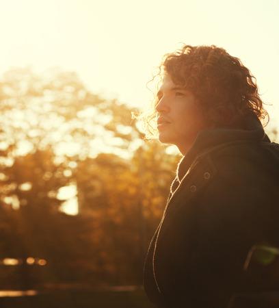 iluminado a contraluz: Hombre joven con el retrato del pelo rizado en el parque de otoño en una puesta de sol, luz de fondo.