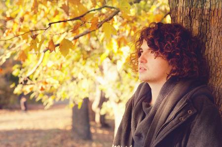oudoor: Young adult man portrait standing near the tree, oudoor in autumn park.