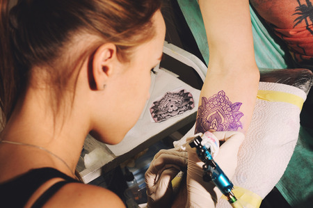 Girl tattoo artist makes tattoo on a hand against purplish blue likeness of a future tattoo using a sketch.