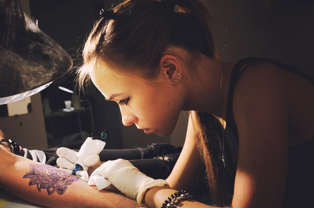 machine: Portrait of a young cute woman master tattooist makes the tattoo on hand on a purplish blue likeness of a future tattoo, under the lamp light.