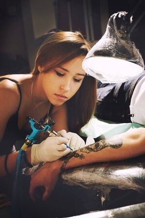 tattooing: Beautiful young girl tattoo artist portrait during creation tattoo on a man`s hand under the lamp light. Stock Photo