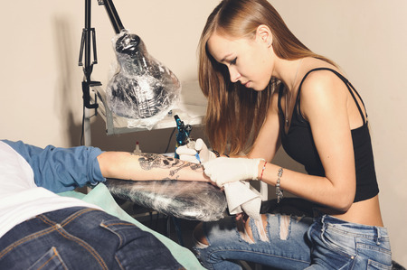 tattooing: Young beautiful woman tattooer showing process of making a tattoo black skull with crown design on a hand. Stock Photo