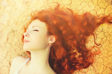 Beautiful young woman portrait with long curly red hair lying on the dried up ground. Stock Photo