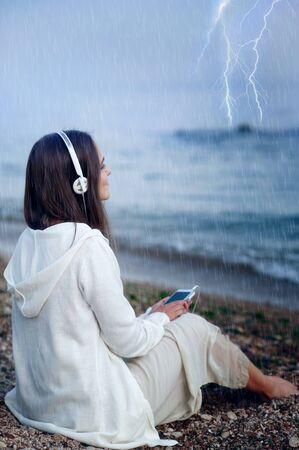 beach rain: Young calm woman relax listening music under rain, sitting on a sea beach. Stock Photo