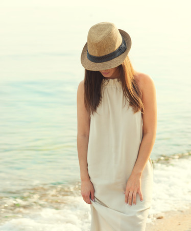 covering: Happy smiling woman walking on a sea beach dressed in white dress and hat covering face, relaxing and enjoy fresh air, outdoor portrait.
