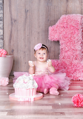 Leuke glimlachende babymeisje dat eerste verjaardagstaart, besmeurd gezicht.