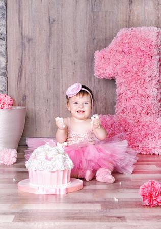 Mignon sourire petite fille mangeant premier gâteau d'anniversaire, le visage barbouillé.