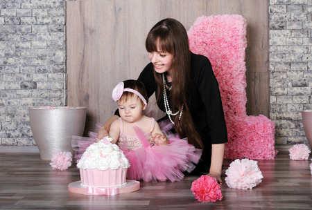Happy mother and daughter celebrating first birthday, mother teach little girl eat a cake.