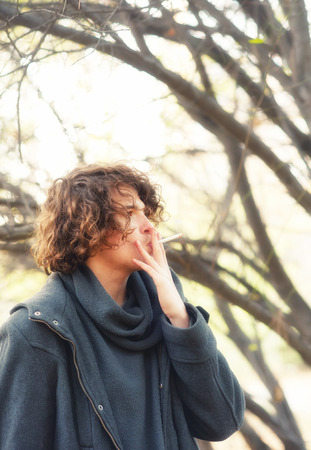 long depression: Young man with curly hairstyle smoking a cigarette outdoor in park