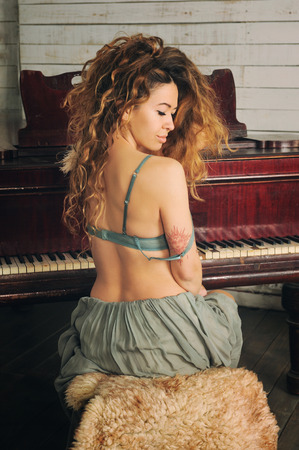 Beautiful sexy woman posing against vintage grand piano, long chic curly hairs Stock Photo