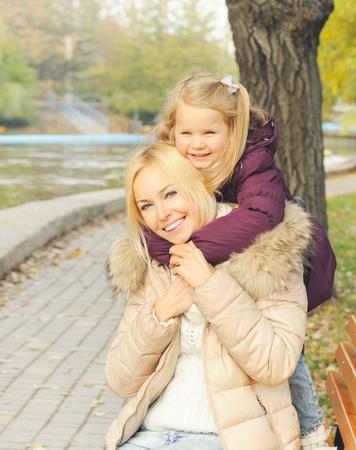niños riendose: linda chica feliz abrazando a su madre al aire libre en el parque.