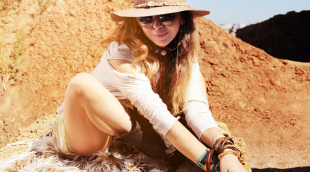 fashion style: Boho style woman portrait sitting on fur, fashion hat, sunglasses and wristbands, sunny outdoor, African safari travel concept Stock Photo