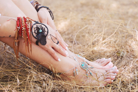 Handcrafted bracelets on a woman legs and hands, dreamcatcher jewelry, close up, white pedicure and manicure, boho chic style, sunny outdoor photo on a straw