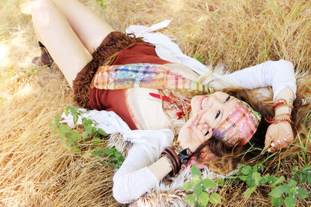 artsy: Dressed in boho chic style woman lying on a hay, sunny day outdoor, healthy and happy lifestyle concept