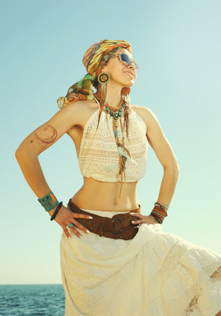 chic woman: Dressed in boho chic style woman portrait, sunny  outdoor photo against sea. Headband, white lace tank top and skirt, leather belt waist and handmade boho jewelry