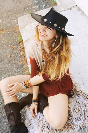 artsy: Outdoor fashion portrait of young beautiful woman sitting on a fur and smiling, hat on a head, boho chic style