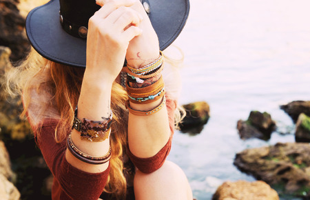 Female hands with boho chic bracelets holding black hat, fashion photo against sea and rock stones, outdoor