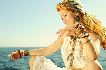 style africain femme de mode portrait en plein air, vêtue de bandeau, débardeur blanc en dentelle haut, collier et boucles d'oreilles, de nombreux bracelets en cuir, se concentrer sur une main Banque d'images
