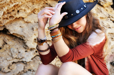 Female hands with boho chic bracelets holding black hat, indie style, stones outdoor backdrop
