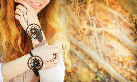 chic woman: Handcrafted bracelets on a woman hands, dreamcatcher jewelry, close up, boho chic style, sunny autumn outdoor, soft colors, copy space for text