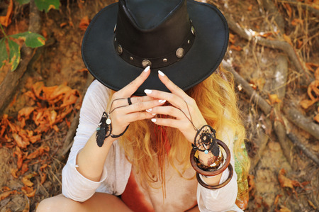 Beautiful female hands with boho chic dreamcatcher bracelets and black leather hat, white  manicure, no face, indie style, autumn outdoor