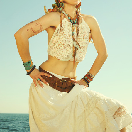 Fashion female neck and hands with boho chic style   leather, beads and feathers bracelets and necklace, white lace tank top and skirt, indie style, bohemian outfit, ocean backdrop