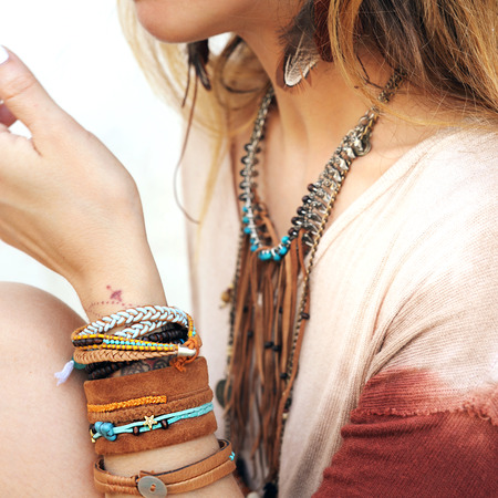 Female neck and hands with many boho bracelets, leather necklace and earrings with feathers, turquoise and brown, outdoor fashion photo