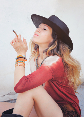 chic woman: Beautiful woman enjoy smoking a cigarette, outdoor photo,  dressed in boho chic style outfit, long hairs, closed eyes, sitting on a street