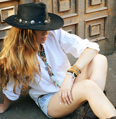 chic woman: Young boho style woman have a rest sitting on a town street against old door, hippie, indie style, chic leather black hat, travel concept