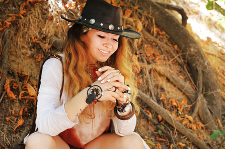 chic woman: Beautiful happy smiling woman with boho chic dreamcatcher bracelets and black leather hat, white  manicure, relaxing in autumn park