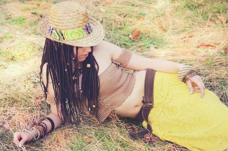 dreadlocks: Retrato de la mujer al aire libre con rastas, vestida con top de punto, falda amarilla y sombrero de paja, que descansa sobre la hierba seca en el parque. ,, Estilo hippie boho indie