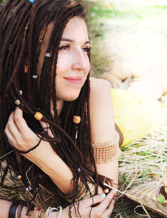 Calm smiling girl portrait with dreadlocks, resting on the dry grass in park, have a beads in her hair Stock Photo
