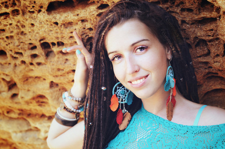 Portrait of a young smiling woman wearing dreadlocks hairstyle, dressed in blue lace dress and blue boho chic dreamcatcher earrings with leather feathers, posing against stone backdrop, looking at camera