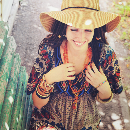 indie: Joyful young woman portrait with dreadlocks dressed in boho style dress and necklace, sunny outdoor, vintage colors