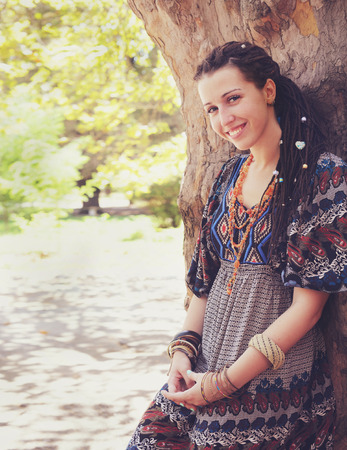 Cute smiling hippie indie style woman with dreadlocks,  dressed in boho style ornamental dress posing outdoor, empty space for text Stock Photo