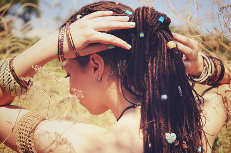 hair back: Beautiful young woman wearing dreadlocks hairstyle gathered in a ponytail and decorated assorted beads, autumn outdoor, focus on a hair Stock Photo