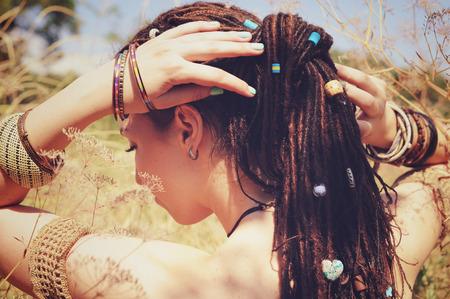 Mooie jonge vrouw die dreadlocks kapsel verzameld in een paardenstaart en versierd assortiment kralen, herfst buiten, focus op een haar