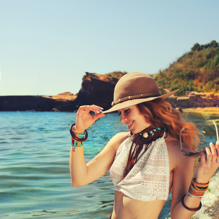 chic woman: Woman traveller hiking near the sea beach, smiling and beautiful, dressed in boho chic bracelets and hat, fashion photo against sea and rock stones, outdoor Stock Photo