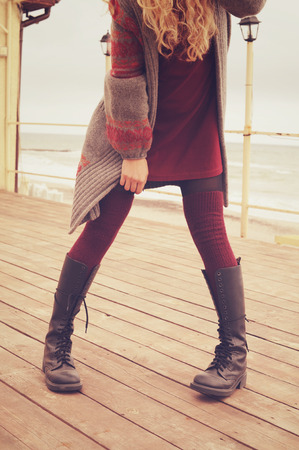 pretty dress: Slim female legs dressed in leather shoes with laces and knitted stockings, gray fashion jersey, short burgundy dress, woman standing on a wooden planking near sea, autumn outdoor fashion, warm colors