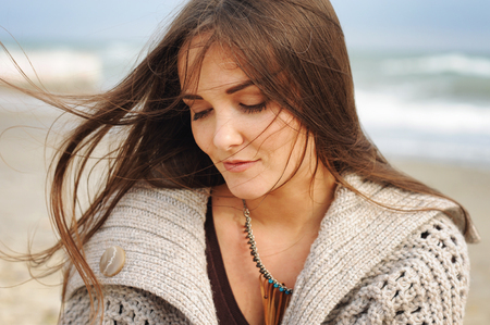 fluttering: Beautiful young happy woman portrait against seascape, long hair fluttering in the wind, looking down, casual autumn fashion, healthy lifestyle Stock Photo