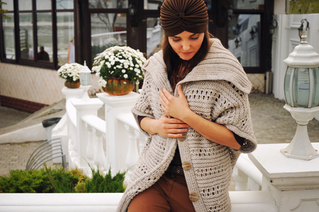 Outdoor portrait of a young woman dressed in fashion hat and cardigan, cute autumn outfit Imagens