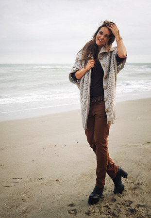 Autumn lifestyle fashion portrait of young stylish hipster woman walking on a sea beach, wearing cute trendy outfit, enjoy weekends and travel Stock Photo