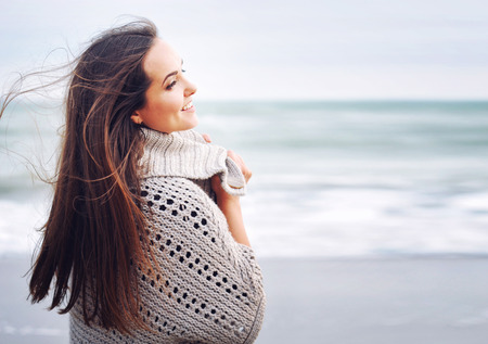 Young beautiful smiling woman portrait against ocean background, winter outdoor Stock Photo