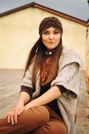 long hairs: Smiling hipster brunette woman sitting, smiling and looking at camera, fashion autumn outfit, hat and cardigan, long hairs, urban style outfit